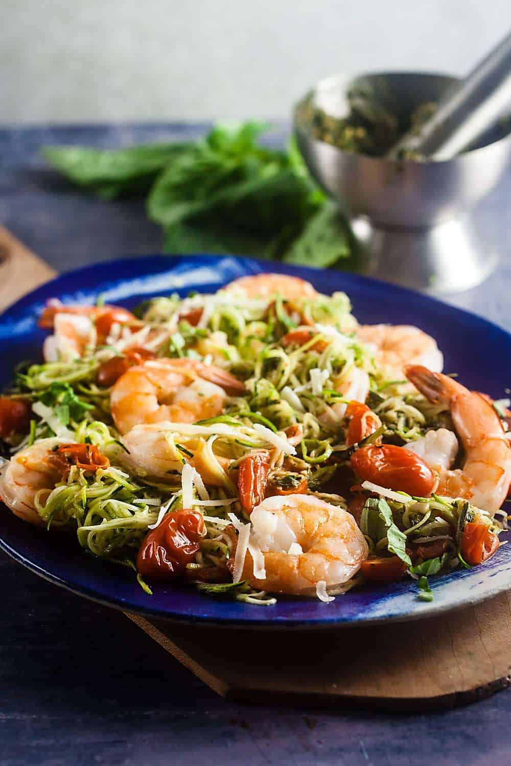 Pesto zucchini noodles with baked shrimp and tomatoes on a blue serving platter