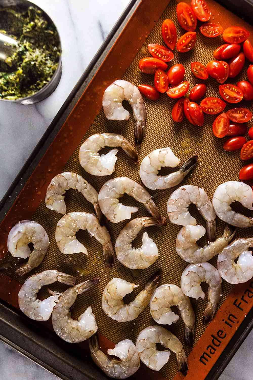 shrimp and tomatoes on a baking sheet
