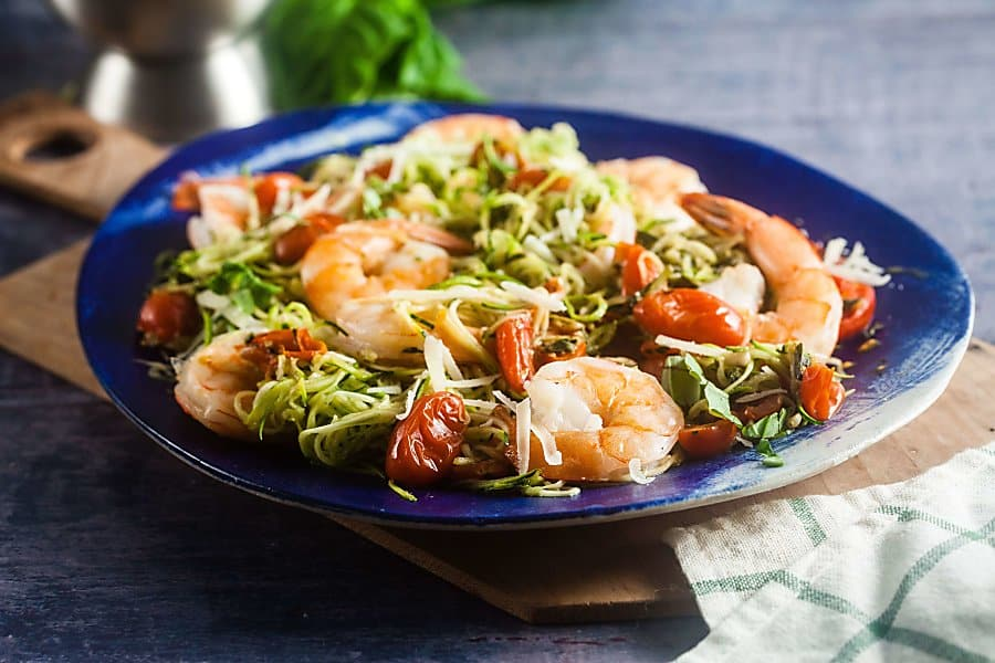 pesto zucchini noodles with baked shrimp on a dinner plate
