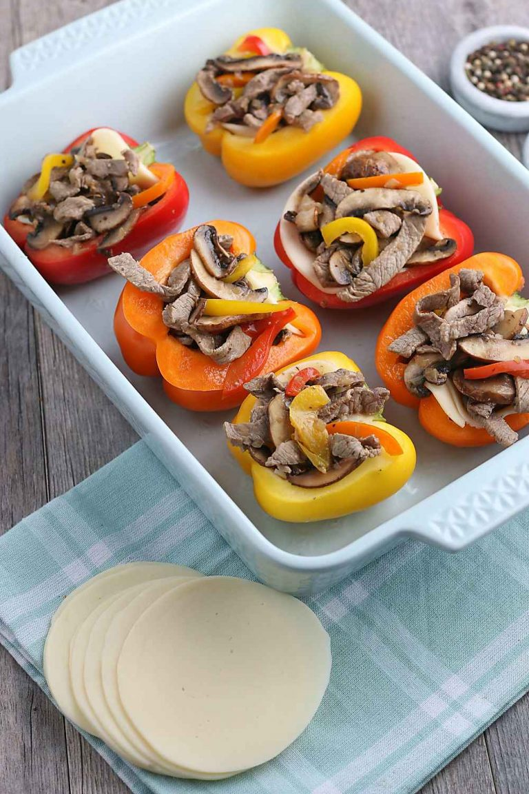 Now the filling for our stuffed peppers is added to the peppers in a pan, ready to be topped with cheese and baked.