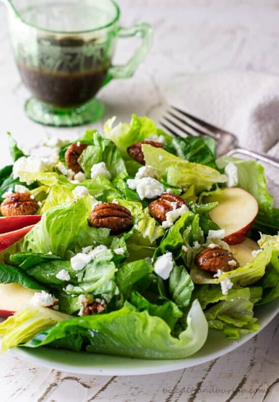 Fall salad with apples and pecans on a plate with a cider dressing to the side