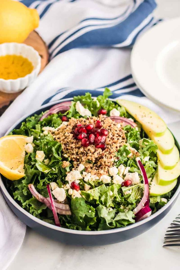 Serving dish filled with kale salad topped with quinoa, pomegranate, and apple slices