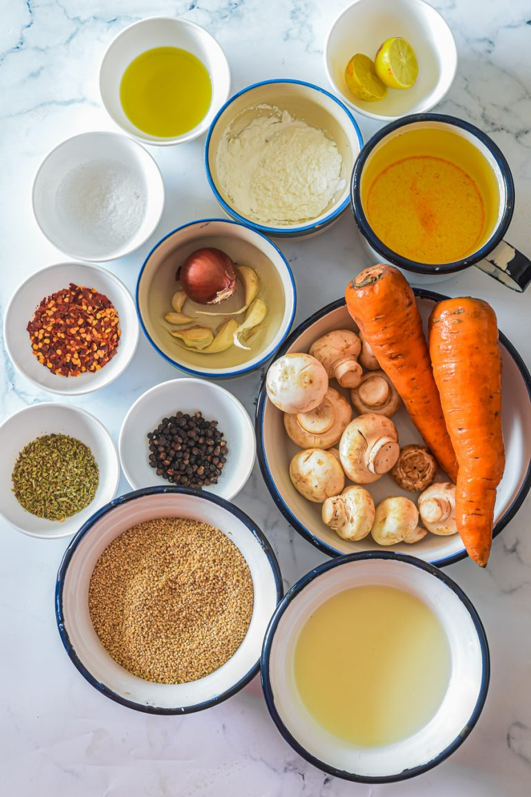 an overhead view of the ingredients needed to make mushroom and quinoa soup, include mushrooms,  quinoa, carrots, coconut milk, broth, fresh herbs, and spices