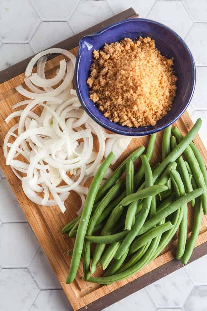 wood cutting board ion a white tile background with ingredients for low car and gluten-free green bean casserole: green beans, onions, and pork panko