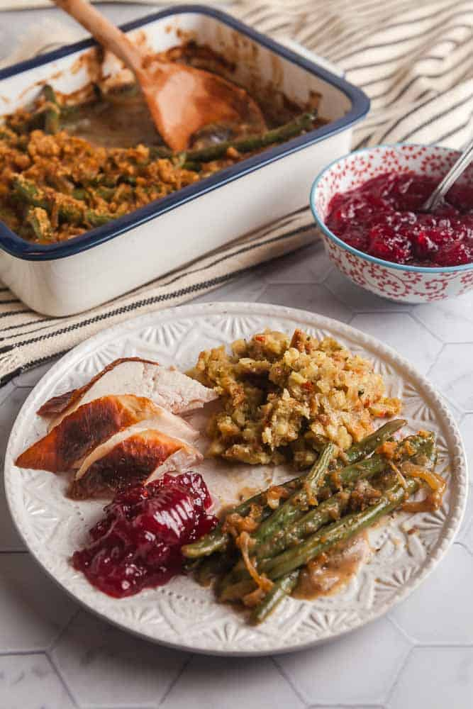 plated chicken dinner with stuffing, healthy green bean casserole, and cranberries