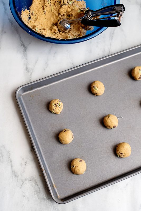 scoop out mint chocolate chip cookie dough on sheet