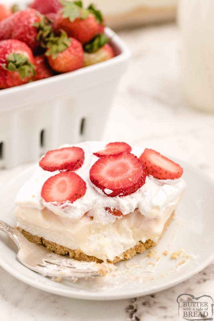 Strawberry Cheesecake Lush is a delicious no bake dessert made with layers of crushed Golden Oreos, pudding, sweet cream and tons of fresh strawberries. Tastes like cheesecake and comes together in minutes for the perfect dessert recipe!