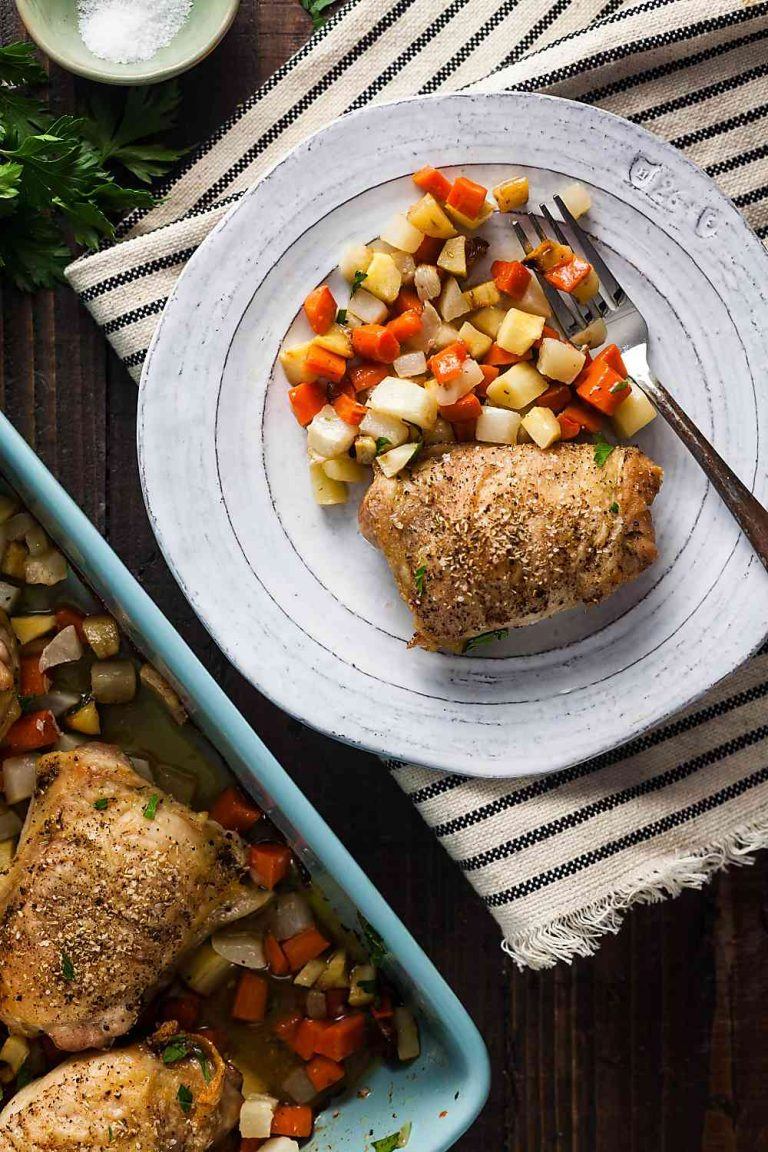 crispy baked chicken thighs with root vegetables on a plate