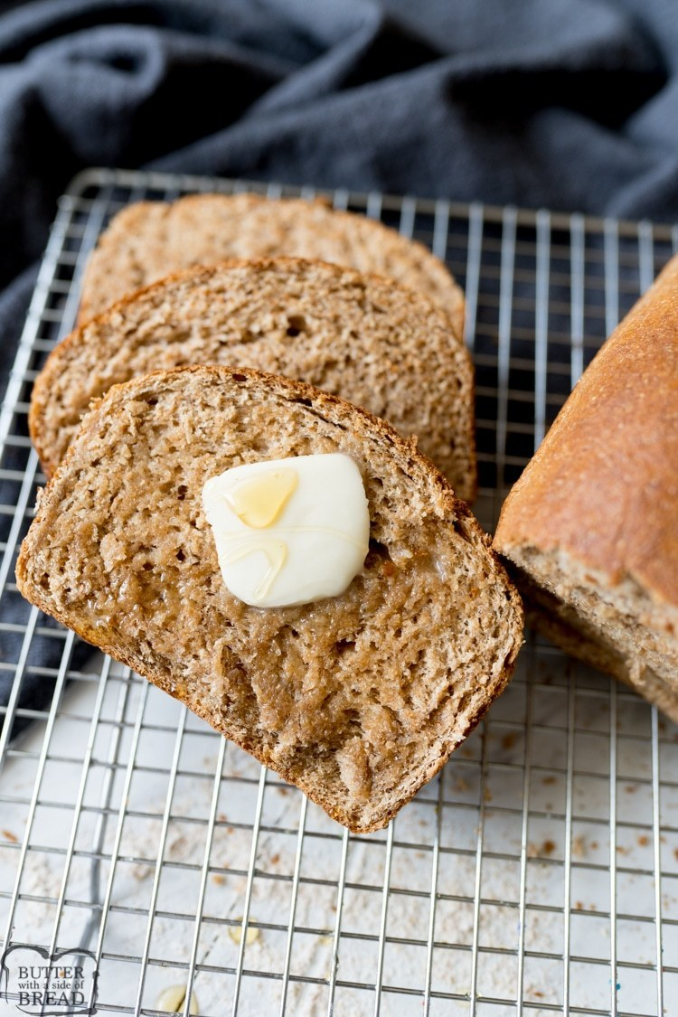honey wheat bread, sliced with butter on it